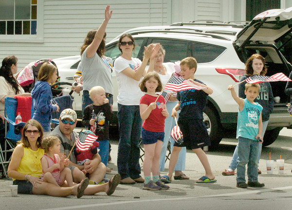 BRYAN EATON/ Staff Photo. Youngsters in front of the East Parish Meeting House waves flags as Salisbury's Memorial Day Parade passes by.