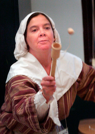 BRYAN EATON/ Staff Photo.Dee Cote demonstrates how to use a ball and cup as she told third-graders at the Cashman School in Amesbury about games in Colonial America. Presenters from Spencer-Peirce-Little Farm were on hand to teach about life in that era.