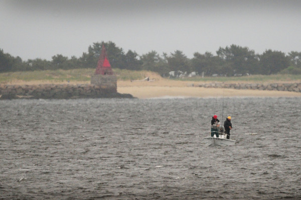 BRYAN EATON/ Staff Photo. Yesterday's damp weather didn't deter these two from fishing in the Merrimack River in a photo taken from Joppa Park on Water Street in Newburyport. Navigating aid Ben Butler's Toothpick at Salisbury Beach State Reservation can be seen to the left.