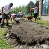 BRYAN EATON/Staff Photo. Students from the Governor's Academy move soil from a raised garden bed to another area of the school grounds at Newbury Elementary School. They're helping to clear the way for an expansion of the playground.