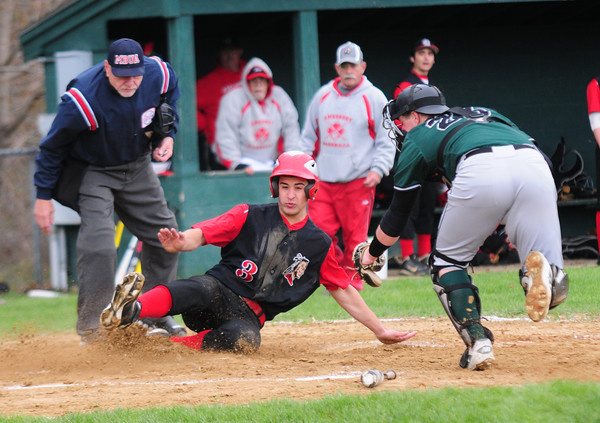 JIM VAIKNORAS/Staff photo Amesbury #3 slides safely into home just under the tag of Pentucket's Jackson KcKean during their game at Amesbury high school Tuesday.