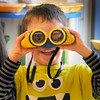 BRYAN EATON/Staff Photo. Max Raimo, 5, stares down a photographer aiming a telephoto lens at him with a pair of binoculars in Susan Simon's pre-kindergarten class at the Bresnahan School. Children were in choice time and Max was amazed how close things looked with the binoculars.