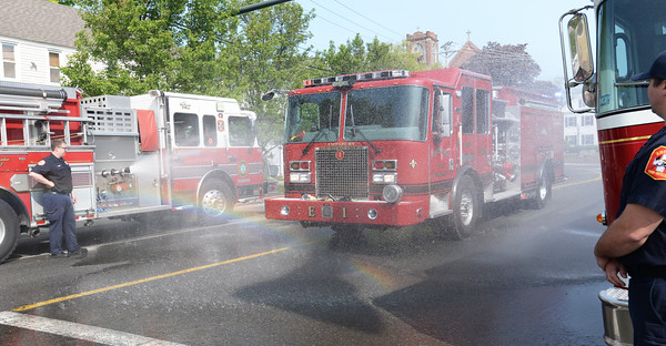 BRYAN EATON/Staff Photo. The Amesbury Fire Department celebrated their new fire Engine One on Friday morning. After a blessing by Rev. Robert Hagopian of the First Congregational Church in Rowley, the engine was christened by driving between to other engines spraying water on it.