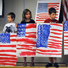 "BRYAN EATON/Staff Photo. Bresnahan School kindergartners hold flags they made in art class while third-grader Theo Roberts, 9, right reads about artist Jasper Johns who was famous for his painting ""Flag"" which he created in the 1950's after being discharged from the army. The Newburyport school were holding their Memorial Day observance Friday morning watching a video about the military and sang ""America."""