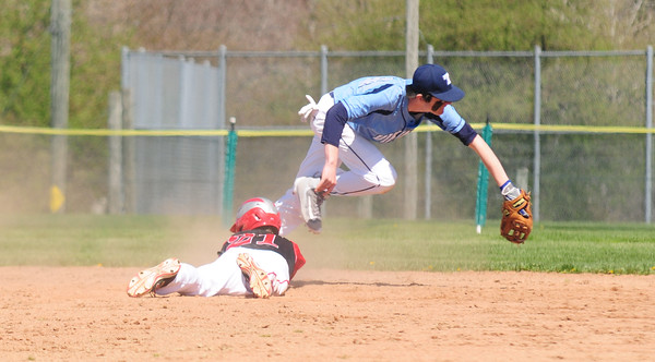JIM VAIKNORAS/Staff photo Triton's Dylan Copland reaches for the throw as Amesbury #21 slides safely into 2nd during their game at Triton saturday.