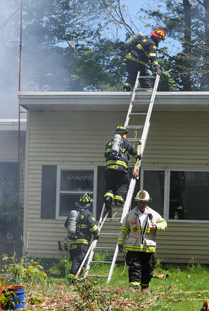 BRYAN EATON/Staff Photo. Firefighters from Amesbury and surrounding towns battle a fire that apparently started in this two-story garage on 22 Fern Avenue in Amesbury and jumped to the rear of the house.