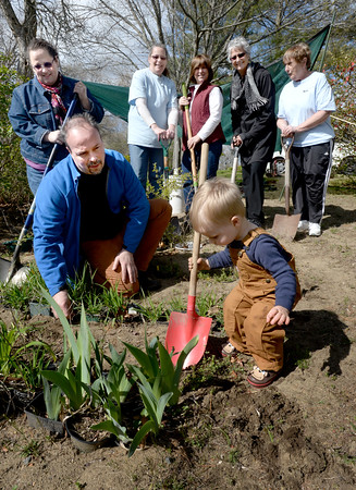 BRYAN EATON/Staff Photo. Toddler Daniel Morris helps his grandfather Doug Morris and other members of the Sea Spray Garden Club promote their plant sale. Back, from left, Donna Morris, Sharon Bolduc, Joanne Woodfall, Suzanne Carpentier and Jan Keough.