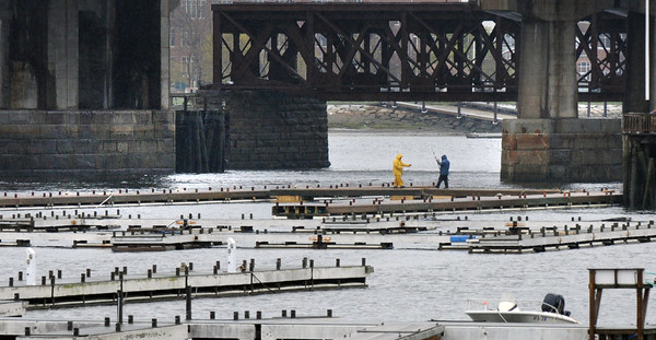 BRYAN EATON/Staff Photo. Workers at Bridge Marina in Salisbury attend to the docks as most of them have been returned to the Merrimack River. Indeed boats are starting to return as well, as boating season is getting closer.