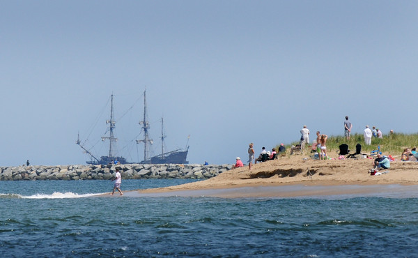 BRYAN EATON/Staff Photo. People at Plum Island Point await the El Galeon which waits for high tide past the south jetty of the Merrimack River.