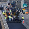 BRYAN EATON/Staff Photo. A paving crew finishes left passing lane of Route One northbound yesterday afternoon. Route One is getting a fresh coat of asphalt from the Gillis Bridge to the Traffic Circle.