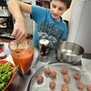BRYAN EATON/Staff Photo. Jared Proulx, 14, mixes tomato sauce for his Mexican meatballs in the cooking class at the Boys and Girls Club in Salisbury. The students were cooking with a Cinca de Mayo theme also making beef or vegetable enchiladas, and chicekn quesadillas.