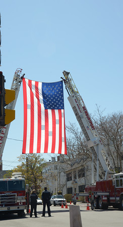 JIM VAIKNORAS/Staff photo A flag hangs from 2 ladder trucks on Green Street in honor of Newburyport firefighter Tony Raven funeral Saturday.