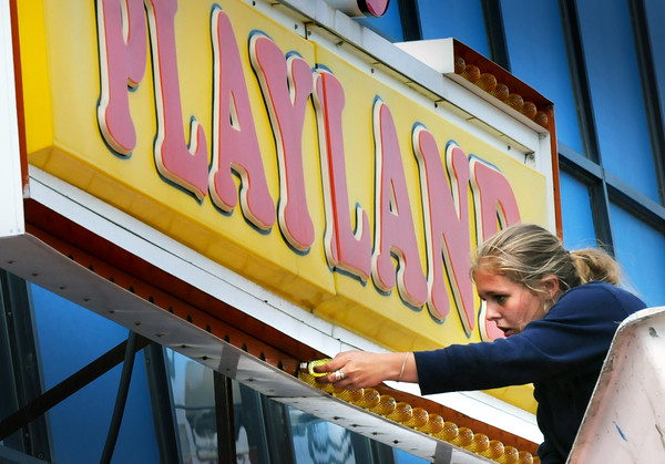 BRYAN EATON/Staff Photo. Morgan Janvrin of Privitera Signs in Groveland replaces the bulbs in one of the signs at Joe's Playland at Salisbury Beach as they get ready for the summer season. The new lightbulbs are energy efficient LED's and are being put in all the signs at the beach landmark.