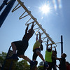BRYAN EATON/Staff Photo. Children are silhouetted by a strong sun on the monkey bars at the Jordan Shay Fitness Playground at the Amesbury Elementary School during physical education. Saturday and Sunday look nice too with the temperature a little cooler later in the weekend.