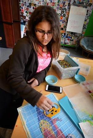 BRYAN EATON/Staff Photo. While some students were playing card games and basketball, Isabel Fudge, 13, and a couple others spent time in the art room at the Newburyport Rec Center. She was creating a pumpkin out of fuse beads Tuesday afternoon.