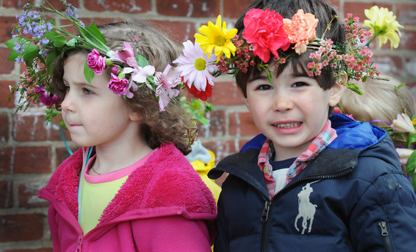 BRYAN EATON/Staff Photo. Addison Hawes, 4, left, and Charlie Chareas, 3, head out on the Newburyport Montessori School's May Day Parade, their heads adorned with flowers yesterday morning. As the weather wasn't cooperating they took their parade to the second floor of Newburyport City Hall for their celebration instead of Brown Square.