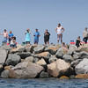 BRYAN EATON/Staff Photo. People line the north jetty at Salisbury Beach State Reservation to watch the ship pass.