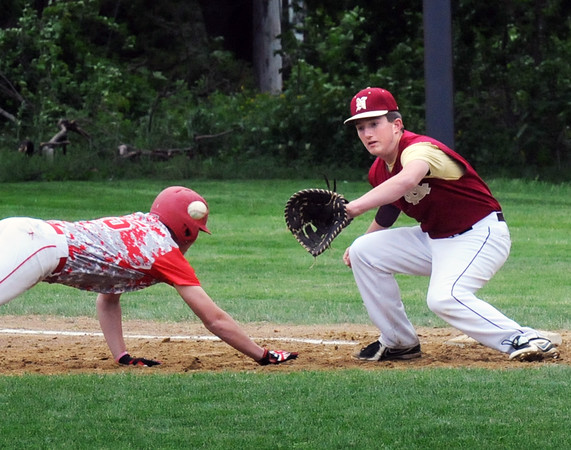 BRYAN EATON/Staff Photo. Newburyport first baseman waits for the throw as Masconomet's 15 makes it back to the base.