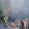 BRYAN EATON/Staff Photo. A firefighter brings what appear to be propane tanks out from the burning garage.