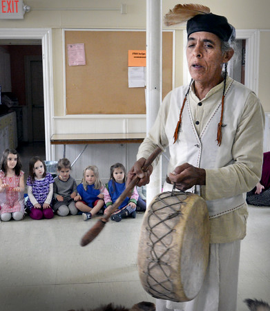 BRYAN EATON/Staff Photo. Eagle Bear from the Apache people of Colorado plays some traditional sounds while chanting on this drum made of animal skins. He was at the Newburyport Montessori School on Monday telling about the life of Native Americans from the west.