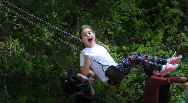 BRYAN EATON/Staff Photo. Recess was certainly outdoors yesterday as the temperature was into the 70's and will continue to stay warm into the weekend. Katie Skafidas, 10, played on the swingset at the playground along with other classmates.