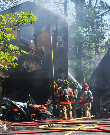 BRYAN EATON/Staff Photo. Firefighters from Amesbury and surrounding towns battle a fire that apparently started in this two-story garage on 22 Fern Avenue in Amesbury and jumped to the back of the house in a breezeway.