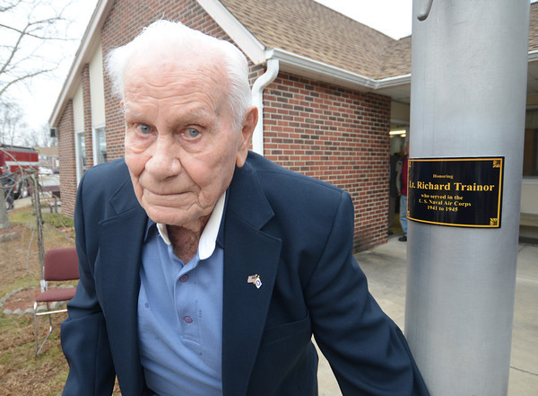 """Salisbury: World War 2 veteran  Richard """"Doc"""" Trainor, poses with a plaque  honoring his at the flag pole at Great Meadows Village Housing Authority. Jim Vaiknoras/staff photo"""