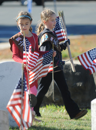 Newburyport: Brownies Katie Pomeroy and Hannah Gross replace flags at Veteran's Cemetary in Newburyport Monday morning. Brownies from across the city took time after the Veteran's Day ceremony to mark graves with flags. Jim Vaiknoras/staff photo