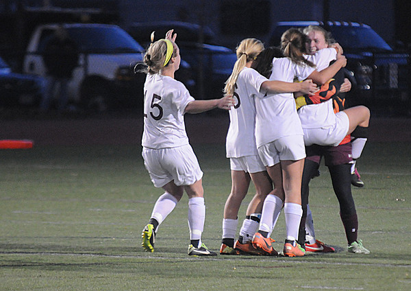 Worcester:Teammates rush to Newburyport goalie Lilly Donovan  after their 1-0 victory over Granby at Foley Stadium in Worcester, giving them the Division 3 State Championship. Jim Vaiknoras/staff photo