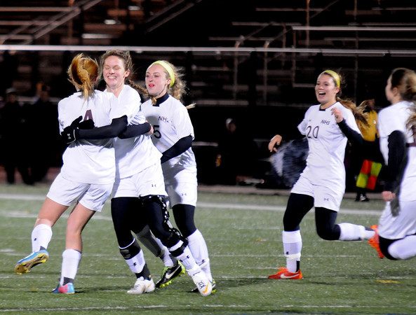 Lynn: Team mates hug Abbie Bresnahan after her 2nd half goal against Bishop Spellman at Manning Field in Lynn. Jim Vaiknoras/staff photo