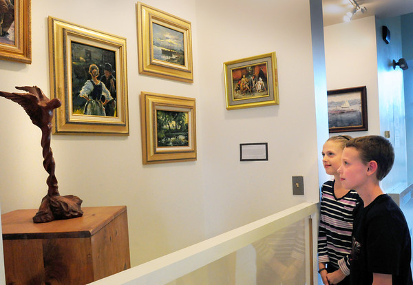 """Rowley: Pine Grove sixth-graders Caitlin White, left, and Keegan Ritchie, both 11, check out artwork of men and women who have served in the armed services in the Pat Marshal Link Gallery. The show is titled """" The HeARTS of our Heroes. Bryan Eaton/Staff Photo"""