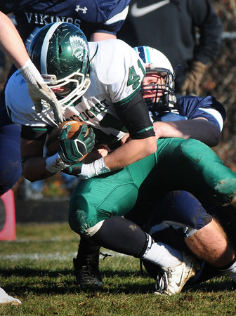 Byfield: Triton's James Ford tackles Pentucket's Andrew Noyes. Bryan Eaton/Staff Photo