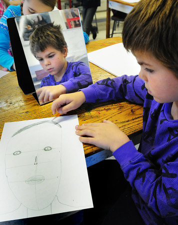 Amesbury: Brody Tonks, 7, uses a mirror as he creates at self-portrait at Amesbury Elementary School. The second-graders in Sara Connor's art class were learning observational drawing and proportion. Bryan Eaton/Staff Photo