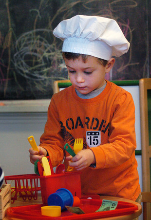 """Newburyport: """"Chef"""" Ryan Carner, 4, puts away kitchen utensils in pre-kindergarten class at the Brown School. He and some friends had been """"making"""" carrot soup and chocolate soup for Thanksgiving. Bryan Eaton/Staff Photo"""