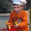 "Newburyport: ""Chef"" Ryan Carner, 4, puts away kitchen utensils in pre-kindergarten class at the Brown School. He and some friends had been ""making"" carrot soup and chocolate soup for Thanksgiving. Bryan Eaton/Staff Photo"