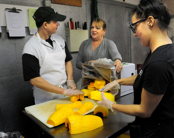 Rowley: Helping out with a Thanksgiving dinner for shut-ins and those in need are Spud's in Rowley employees, from left, kitchen manager Chris Hassapis, assistant manager Jan Addison and bartender Barbara Moore. Bryan Eaton/Staff Photo