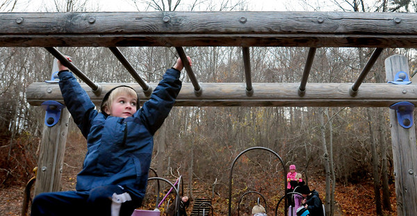 Amesbury: Zev Wysocki, 7, eyes his next move on the monkey bars at Amesbury Elementary School on Tuesday. He was at the Amesbury Recreational Department's Afterschool Program. Bryan Eaton/Staff Photo