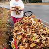 Newburyport: Louise Duda didn't mind the rain, or warm weather, as she cleaned up leaves in front of her Spofford Street home in Newburyport on Thursday. The weather turns sunny today, though with more seasonable temperatures. Bryan Eaton/Staff Photo