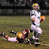 BRYAN EATON/ Staff Photo. Newburyport's James Gallo grabs on to North Reading's John Merullo for the tackle.