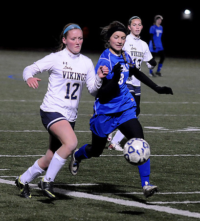 JIM VAIKNORAS/Staff photo  Georgetown's Amanda Saffer chases the ball with East Bridgewater's Jackie Gavin during their game at Manning Field in Lynn. Georgetown lost the game 2-0.