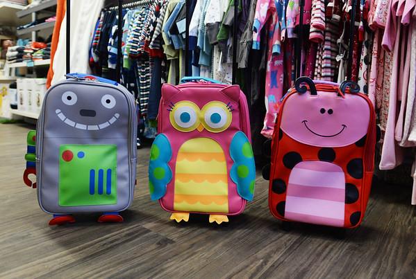 BRYAN EATON/ Staff Photo. Kids rolling luggage at Lively Kids.