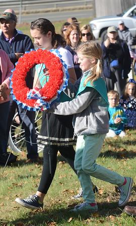 JIM VAIKNORAS/Staff photo Alanna Egan. 10, and Elizabeth Boelke, 9, help lay a wreath during the annual Veteran's Day ceremony at Veteran's Cemetery in Newburyport.