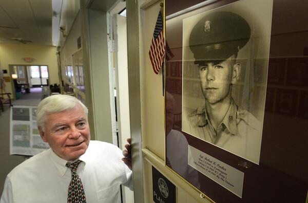 BRYAN EATON/Staff Photo. Newburyport Veteran's Agent Kevin Hunt stands under a photo of Sgt. Robert K. Parker of Newburyport who was killed in action in the Vietnam Conflict.