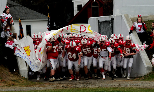 JIM VAIKNORAS/Staff photo Amesbury's football team crashes through a banner at the start of their game against Newburyport Thursday The Indians won the game  22-17.