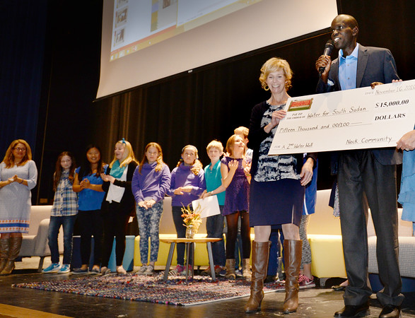 BRYAN EATON/Staff photo. Salva Dut, one of the Lost Boys of Sudan, with Nock principal Lisa Furlong, accepts $15,000 to help with water in Sudan.