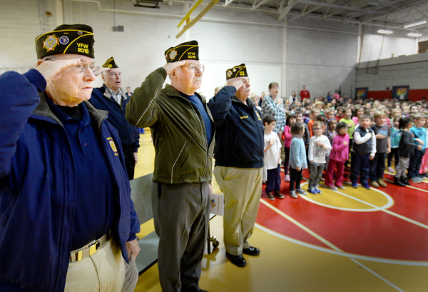 BRYAN EATON/Staff photo. The Cashman School student council held a Veteran's Day Assembly on Thursday with several Viet Nam veterans in attendance, here saluting during the Pledge of Allegiance. From left, Henry Cross in the navy, Sky Iworksky in the marines, and Bill Burnham in the navy.