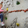 BRYAN EATON/Staff photo. Kaitlyn Cook, 7, looks for her next foothold on the climbing wall in Margaret Welch's physical education class at Amesbury Elementary School. November is their climbing wall challenge where the first-graders see how many times they can complete the course when they participate.