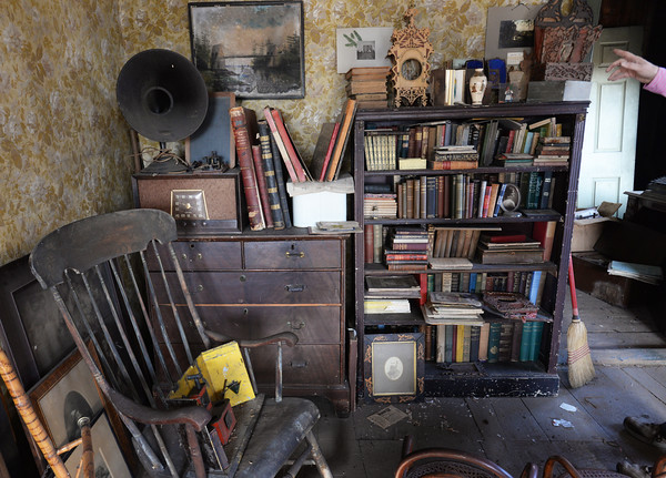 BRYAN EATON/Staff photo. Room upon room are filled with books, furniture and old photographs.