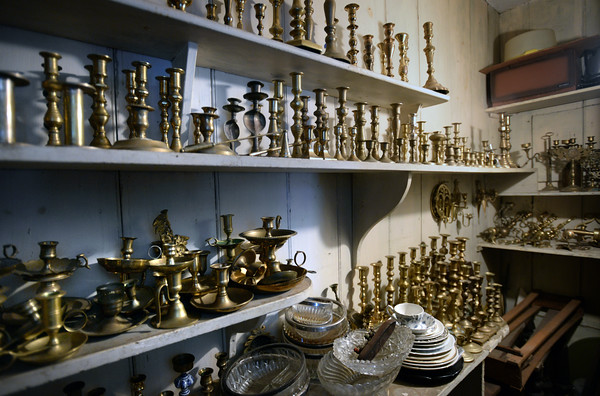 BRYAN EATON/Staff photo. Brass candle holders and other objects fill a large closet in the house.