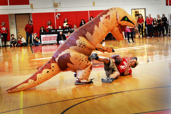 """BRYAN EATON/Staff photo. """"Clipposaurus Rex"""" attacks an Amesbury High football player during their Color Day on Wednesday in which each class puts on a skit poking fun at rival Newburyport High. An """"Amesbrosaurus Rex"""" then appeared to defeat the Newburyport dinosaur, Amesbury students hoping their football team does the same to Newburyport during the Thanksgiving Day football game."""